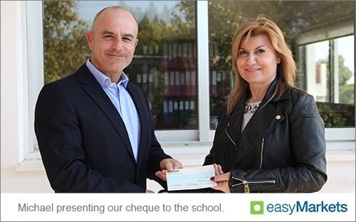 easyMarkets donates cheque to school